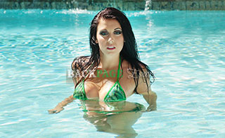 Brunette goes for a swim in the pool in a bikini.