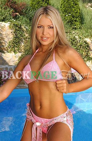 Blonde poses next to the water in a pink bikini.