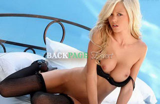 Blonde poses in seductive way with bra pushed down.