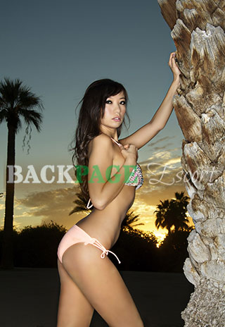 Asian poses against palm tree at sunset in swimsuit.