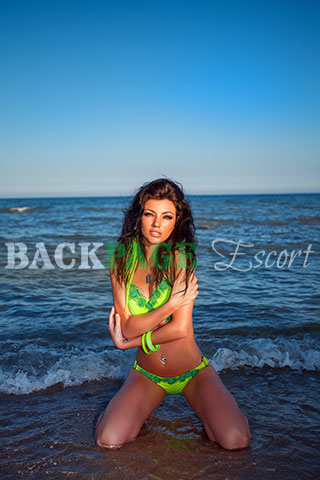 Brunette poses on her knees at the beach in a swimsuit.